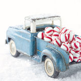 Old toy truck carrying peppermint candy. Old blue toy truck carrying striped peppermint candy on white snowy bakcground Royalty Free Stock Images
