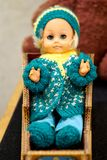Old toy is a vintage doll with blue eyes in a woolen hat sitting in a sleigh. Subject from the past. Shallow depth of field royalty free stock images