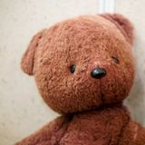 Old toy - vintage plush brown bear. Portrait. Shallow depth of field stock image