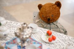 Old toy - a vintage plush brown bear sits at a puppet table. Subject from the past royalty free stock photos