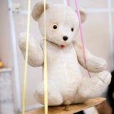 Old toy - vintage white plush bear sitting on a swing royalty free stock photos