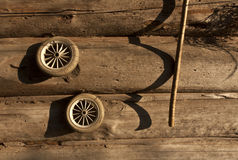 Old toy wheels and log house wall. Royalty Free Stock Image