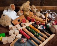 Old toys. Abandoned old toys against an antique wooden chest royalty free stock photos