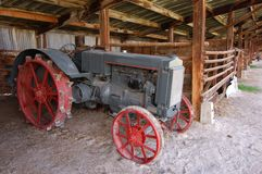 Old tractor. Sitting in a barn Stock Photos