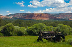 Old tractor in an Arizona field. An old tractor left in a field of grass with a magnificient view of an Arizona mountain range Stock Image