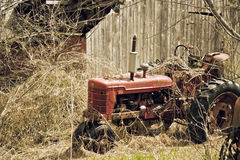 Old Tractor and Barn. Old tractor setting behind a falling down barn. Times gone by royalty free stock photos