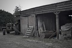 Old tractor and barn. Old Tractor sits next to an un used barn black and white royalty free stock photos