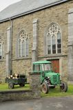 Old tractor and church, ardennes Royalty Free Stock Photography