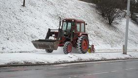 Old tractor cleaning snow street pedestrian sidewalk winter car. Old tractor clean snow from street sidewalk and cars pass in winter. Industrial city care stock video