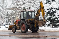Old tractor cleans snow on city Stock Images