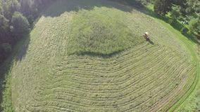 Old tractor cut grass from meadow, aerial view stock video footage