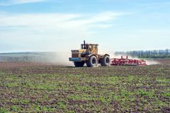 An old tractor is dragging a modern aggregate for tillage leveling the field surface. And interrupting weeds Stock Photography