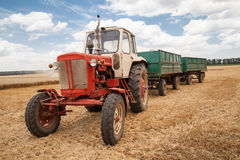 Old tractor in field, against a cloudy sky Stock Photo