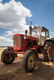 Old tractor on the field, against a cloudy sky Stock Photography