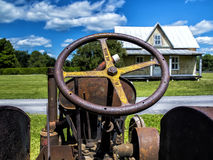Old tractor in front of an old farm with tin roof Stock Photo