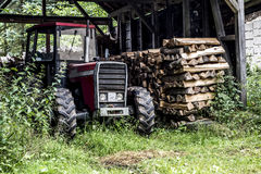 Old tractor front view in germany countryside old abandoned barn firewood wood stacked Royalty Free Stock Images