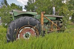 Old tractor in long grass has a loader Stock Images