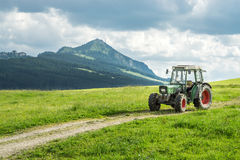 Old tractor on meadow. Beautiful mountain view in the Alps. Old tractor on a meadow with fresh grass. Beautiful view to alpine mountains. Alps Royalty Free Stock Images