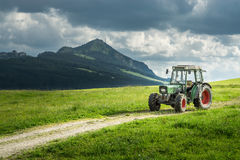 Old tractor on meadow. Beautiful mountain view in the Alps. Old tractor on a meadow with fresh grass. Beautiful view to alpine mountains. Alps Stock Photo