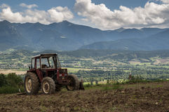 Old tractor in mountain landscape Stock Image