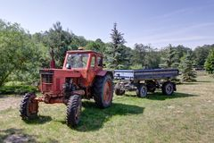 Old Tractor. This photo shows an old red tractor with a blue trailer Royalty Free Stock Photo
