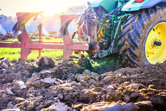 Old tractor ploughing soil in the agricultural field Stock Photos