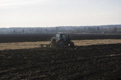The old tractor ploughs up the earth. The old tractor of dark blue colour ploughs up the earth Royalty Free Stock Photo