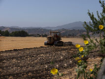 Old Tractor plowing. Field, with yellow straws on one side and black soil on the other.  Hills in the background, yellow wild flowers on the side. Middle of Stock Images