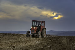 An old tractor plowing the field. During sunset Royalty Free Stock Images