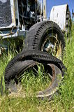 Old tractor rims, wheels, and tires. The steel wheels steel wheels and rims of tractors and  equipment are in rows of a field of long grass Stock Photos