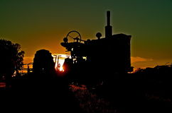 Old tractor silhouetted. An old tractor is silhouetted in the sunset Royalty Free Stock Photo