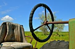Old Tractor Steering Wheel. The seat and steering wheel of an old tractor reflect hours of time spent by a farmer in the field Royalty Free Stock Image