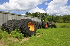 Old tractor tires stacked against old building Stock Images