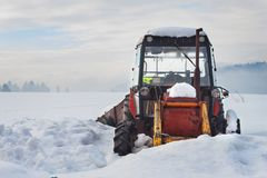 Old tractor under the snow. Snow calamity in transport. Frozen diesel engine. Stock Photos