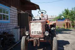 An old tractor in a village courtyard. Close-up Royalty Free Stock Images