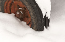 Old tractor wheel in snow. Royalty Free Stock Photography