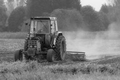 Old  tractor working field in B&W Royalty Free Stock Images
