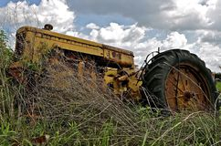 Old Tractors partially covered by weeds Stock Photo
