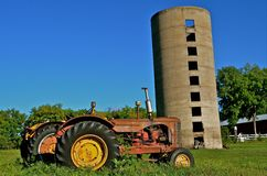 Old Tractors and Silo. Several very old tractors are parked to a vintage poured concrete silo Royalty Free Stock Images