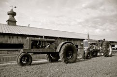 Old tractors by a steel building Royalty Free Stock Photo