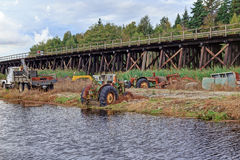 Old tractors and truck at riverside by a railway Stock Image