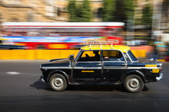 Old traditional black and yellow taxi in movement depicted with motion blur panning
