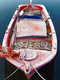 An Old Traditional Greek Fishing Boat Tied up in Village Harbour. An old traditional hand made small Greek fishing boat, or caique, with faded orange marine stock photos
