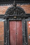 Old traditional handcrafted wooden door in the brick wall Stock Photos