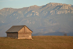 Old traditional hay barn in the mountain area with a background a mountain range.  Stock Photo