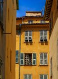 Old traditional houses in the narrow streets in the Old Town Vielle Ville in Nice in the South of France. View of old traditional houses in the narrow streets in royalty free stock photography
