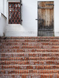 Old traditional porch with brick stairs and locked wooden door Royalty Free Stock Images