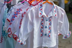 Old traditional Romanian folk costumes with embroidery, specific. For kids and exposed for sale at one traditional fair royalty free stock photography