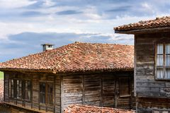 Old traditional rustic houses in Zheravna, Bulgaria. Zheravna, Bulgaria - Two authentic rustic house made of stone and wood with tile roofs against the cloudy royalty free stock photo