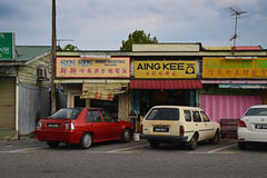 Old traditional shop houses at a small town in Malaysia with cars parked in front Stock Photo